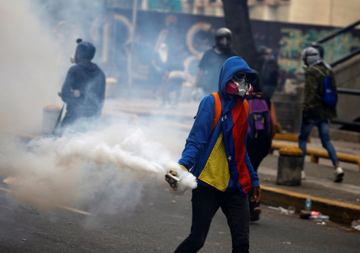 "An opposition demonstrator carries a gas grenade while clashing with riot police during the so called ""mother of all marches."