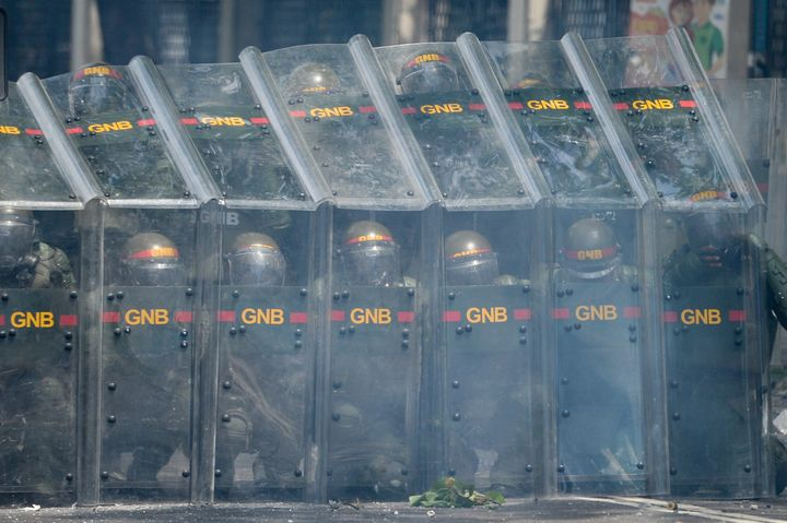 Riot police officers confront demonstrators in Caracas.