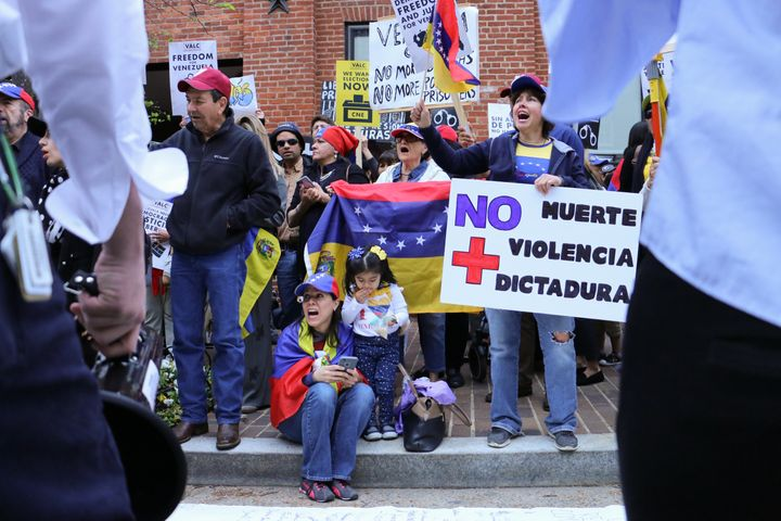 "A protester outside the Venezuelan embassy in Washington DC holds a sign reading ""no more death, violence, dictatorship"""