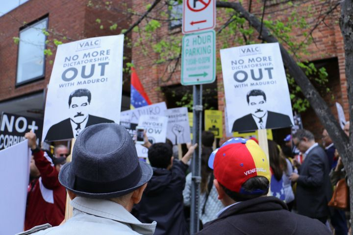 onlookers at the Venezuelan embassy in Washington DC observe signs calling for the removal of president Nicolás Maduro