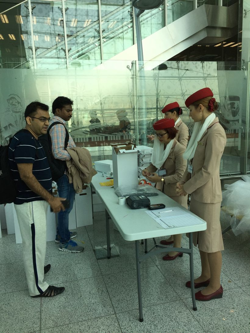 Emirates staff allowing travelers to check-in their laptops