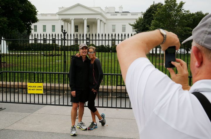 Tourists have their photograph taken from the sidewalk at the White House. The sidewalk will now be off-limits around th