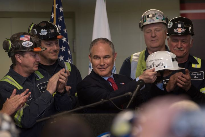 EPA administrator holds up a miner's helmet that he was given after speaking with coal miners at the Harvey Mine on Apri