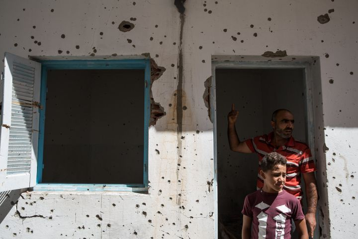 Extremism is no stranger to Tunisia. Here, two Tunisians visit a house damaged during a shootout between the army and suspected terrorists in their hometown.