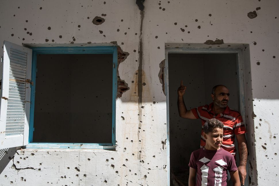 Extremism is no stranger to Tunisia. Here, two Tunisians visit a house damaged during a shootout between the army and suspect