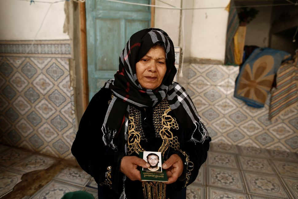 A Tunisian woman holds a photo and passport of her son, who is suspected of joining ISIS in Libya.