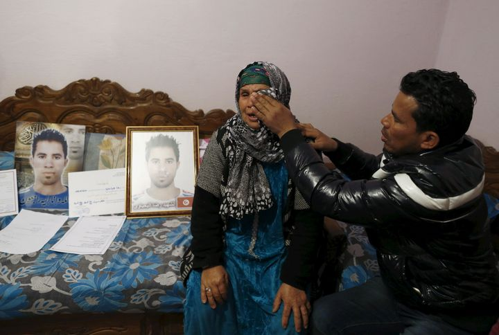 A young man wipes away his mother's tears as she mourns the death of her son, who took his own life after being refused a job.