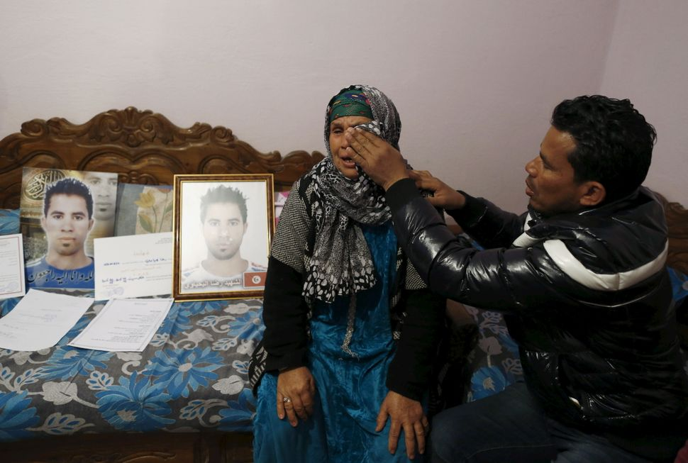A young man wipes away his mother's tears as she mourns the death of her son, who took his own life after being refused a job