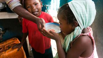 A young girl drinks water from a bowl at a public fountain during a period when the public water supply has been cut off, in the  Isotry district of Antananarivo, Madagascar on March 17, 2017.  As usual, they get up before dawn and, one by one, place their cans in a neat row at the base of the water pump, ready for another long day of waiting and carrying.For the water carriers of Antananarivo, the capital of Madagascar, distributing water is a daily physical struggle that has been worsened by regional drought and climate change.  / AFP PHOTO / RIJASOLO        (Photo credit should read RIJASOLO/AFP/Getty Images)