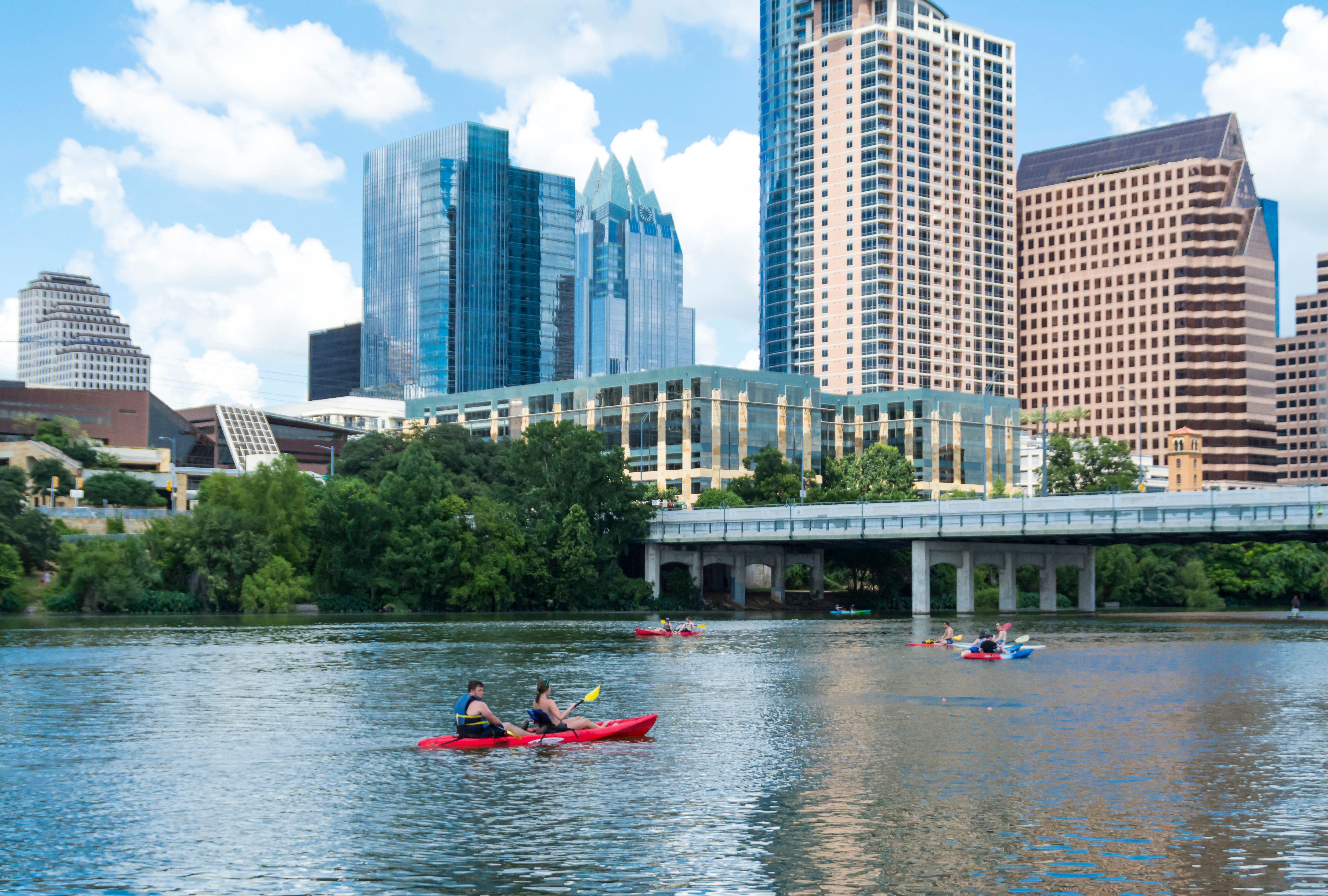 People canoeing on Lady Bird Lake in Austin with the Austin Skyline in the background.