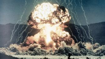 (Original Caption) Ground level view of a surface test of a nuclear device. Slide shows the beginning of a mushroom cloud, glowing intensly white, with lightning arcing from the ground to converge above the explosion. Undated color slide.
