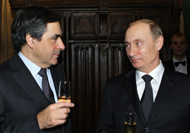 Russian Prime Minister Vladimir Putin (R) and Francois Fillon speak in a restaurant in Moscow, late on...