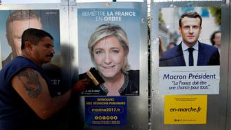 Sauveur, a member of the French National Front (FN) political party pastes a poster on an official billboard for French National Front (FN) political party leader Marine Le Pen next to the poster of  Emmanuel Macron (R), head of the political movement En Marche! (Onwards!), as part of the 2017 French presidential election campaign in Antibes, France, April 14, 2017.  REUTERS/Eric Gaillard