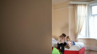 A young mother and daughter sit on a bed in a dingy woman's support centre
