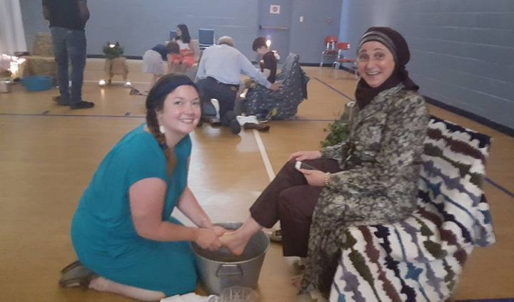Rebecca Hart, a member of The Grove, washes the feet of Lina Sanjak, a volunteer.