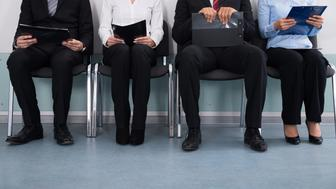 Close-up Of Businesspeople With Files Sitting On Chair