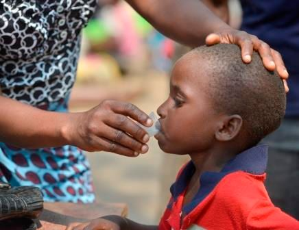 <em>A young boy takes antibiotic medication for trachoma. </em>