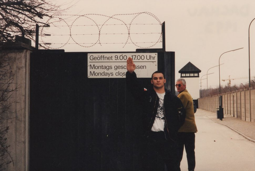 Christian Picciolini doing a Nazi salute outside the gates of Dachau, a former concentration camp in