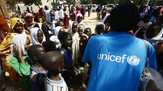 A UNICEF employees speaks to children at the El-Riyadh camp for internally displaced persons (IDP) in Geneina, the capital of the state of Sudan's West Darfur, on February 8, 2017. / AFP / ASHRAF SHAZLY        (Photo credit should read ASHRAF SHAZLY/AFP/Getty Images)