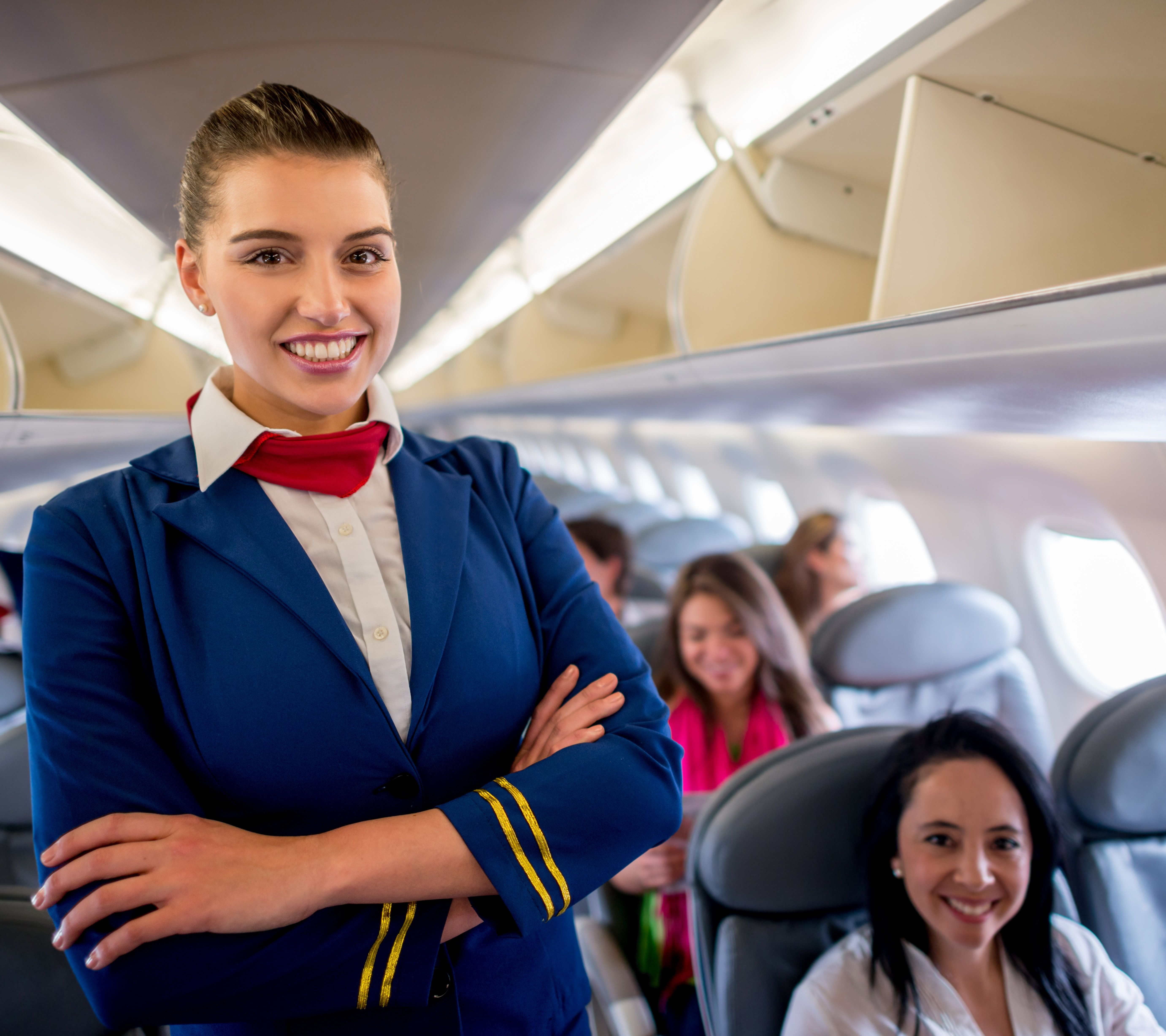 Flight attendant onboard with a group of passengers in the plane