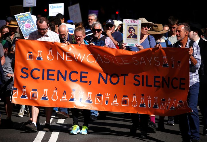 Protesters hold placards and banners as they participate in Saturday's March for Science rally on Earth Day, in central Sydne