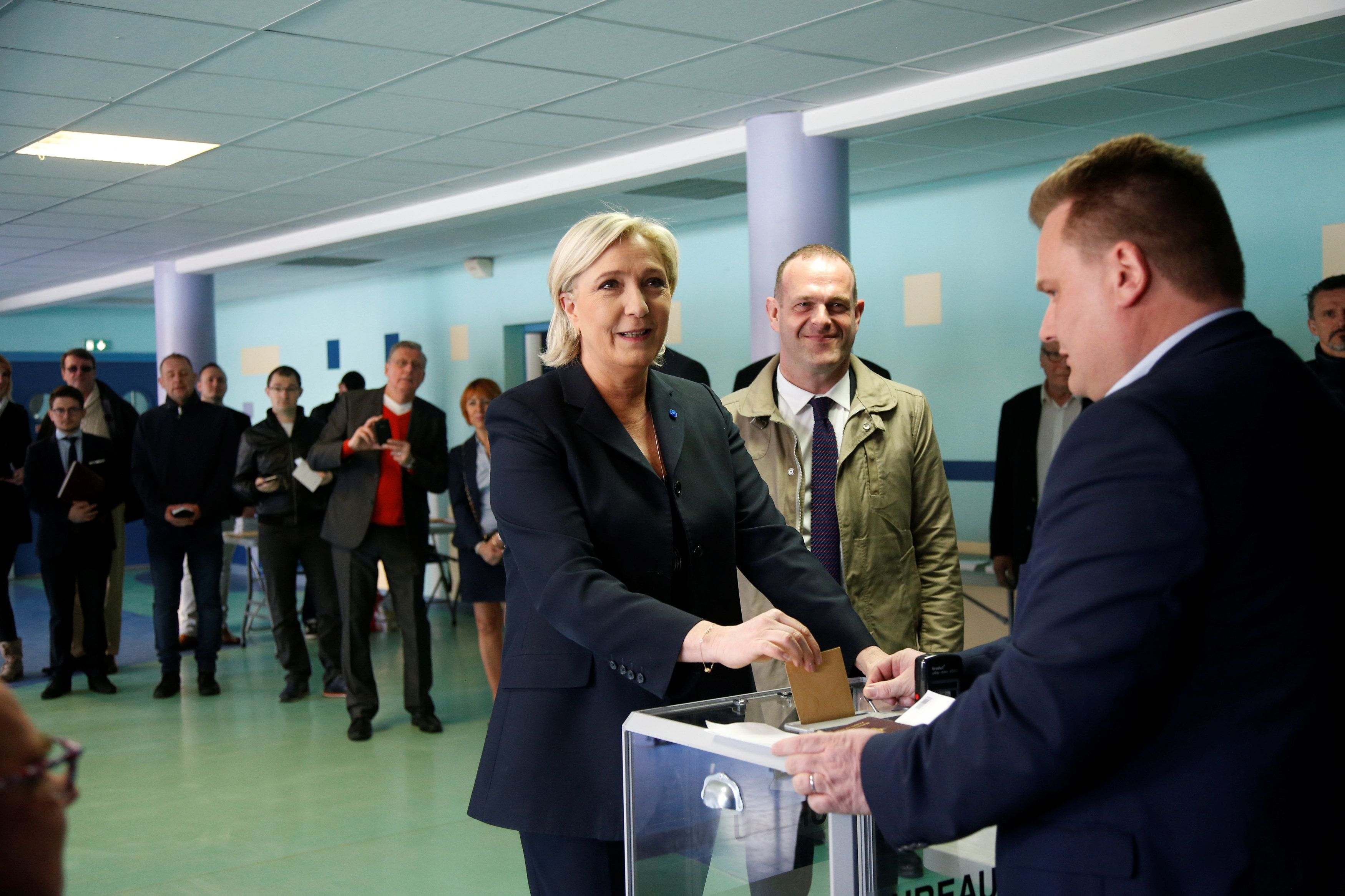Marine Le Pen (C), French National Front (FN) political party leader and candidate for French 2017 presidential election, casts her ballot in the first round of 2017 French presidential election at a polling station in Henin-Beaumont, northern France, April 23, 2017. At R, Mayor of Henin-Beaumont Steeve Briois REUTERS/Charles Platiau