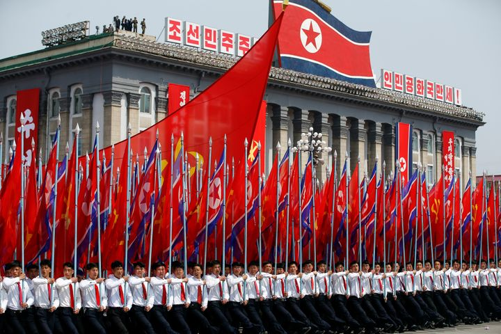 Men carry flags in front of the stand with North Korean leader Kim Jong Un and other high ranking officials during a military
