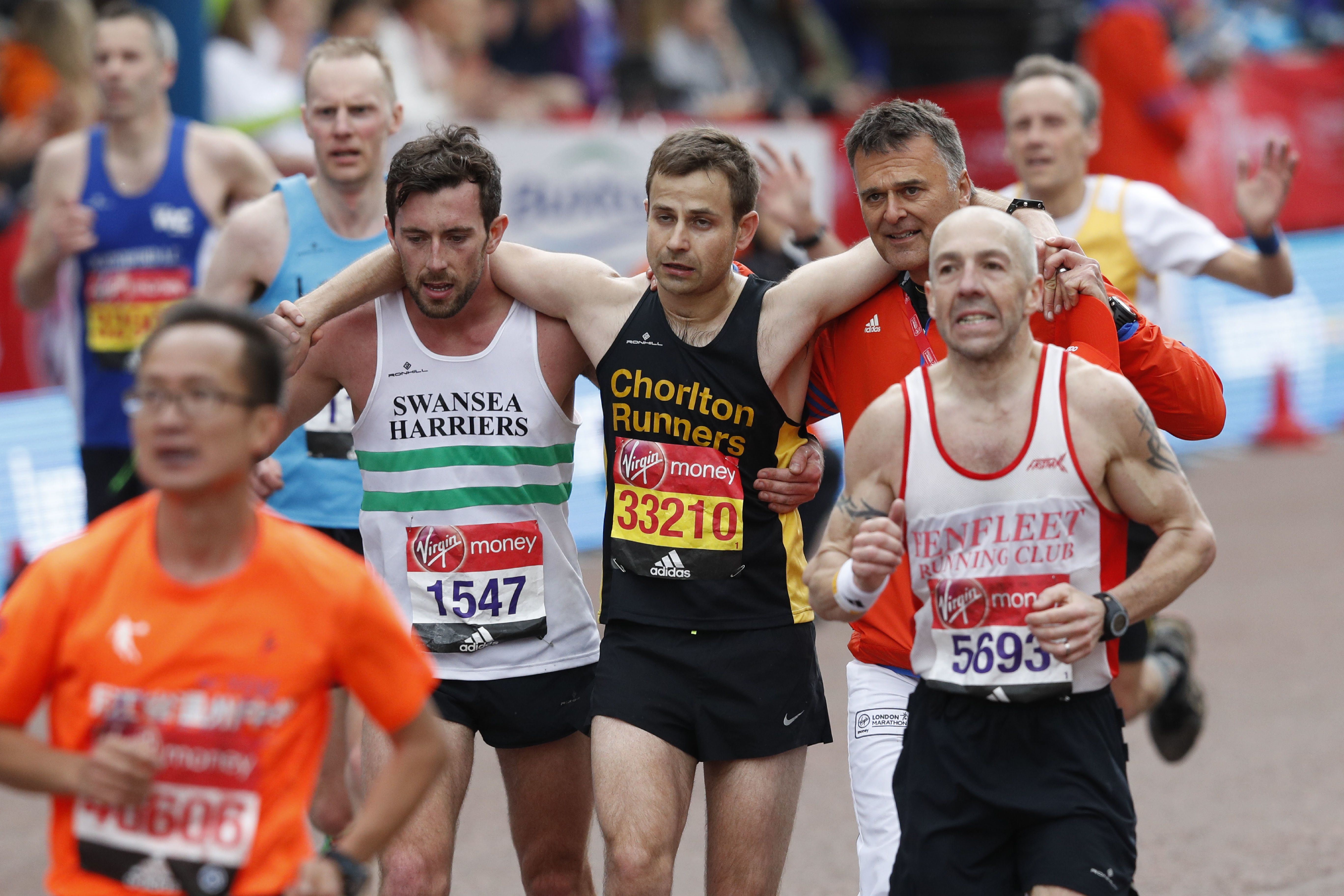 Matthew Rees (L) of Swansea Harriers helps David Wyeth (C) of Chorlton Runners reach the finish line during the London marathon on April 23, 2017 in London. / AFP PHOTO / Adrian DENNIS        (Photo credit should read ADRIAN DENNIS/AFP/Getty Images)