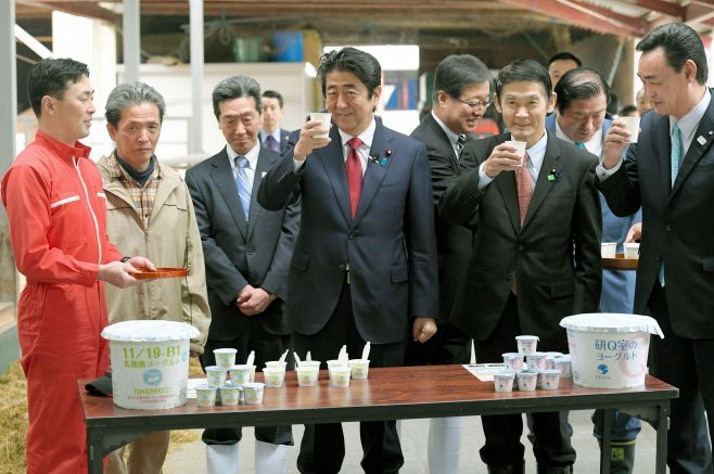 Japanese Prime Minister Shinzo Abe drinks milk during his visit to a cattle ranch that reopened after Fukushima nuclear crisi