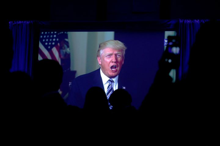 Guests watch a video of U.S. President Donald Trump as he addresses the 15th Plenary Assembly of the World Jewish Congress in