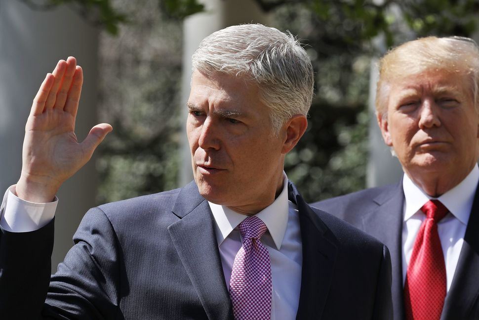 U.S. Supreme Court Justice Neil Gorsuch takes the judicial oath as Trump looks on during a ceremony in the Rose Garden at the