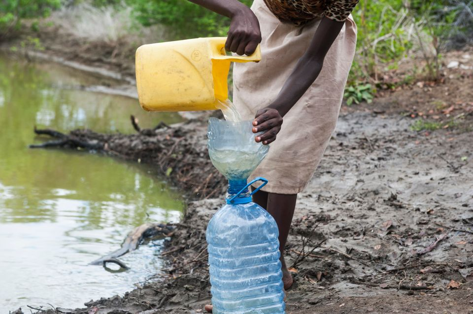 A young girl fills a plastic container full of water from a small riverbed, which she will then transport back to her home vi