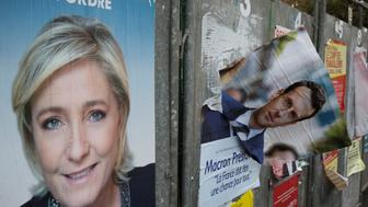 A picture taken on April 24, 2017 in Henin-Beaumont, northern France, shows campaign posters of French presidential election candidate for the far-right Front National (FN) party Marine Le Pen and candidate for the En Marche ! movement, Emmanuel Macron, one day after the first round of the Presidential election. Pro-European Emmanuel Macron is set to face far-right candidate Marine Le Pen in France's presidential run-off, results showed on April 24, making him clear favourite to emerge as the country's youngest leader in its history. / AFP PHOTO / JOEL SAGET        (Photo credit should read JOEL SAGET/AFP/Getty Images)