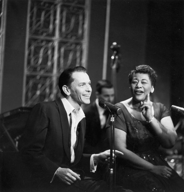 American singers Frank Sinatra and Ella Fitzgerald sit next to each other, singing in front of microphones on a television sp