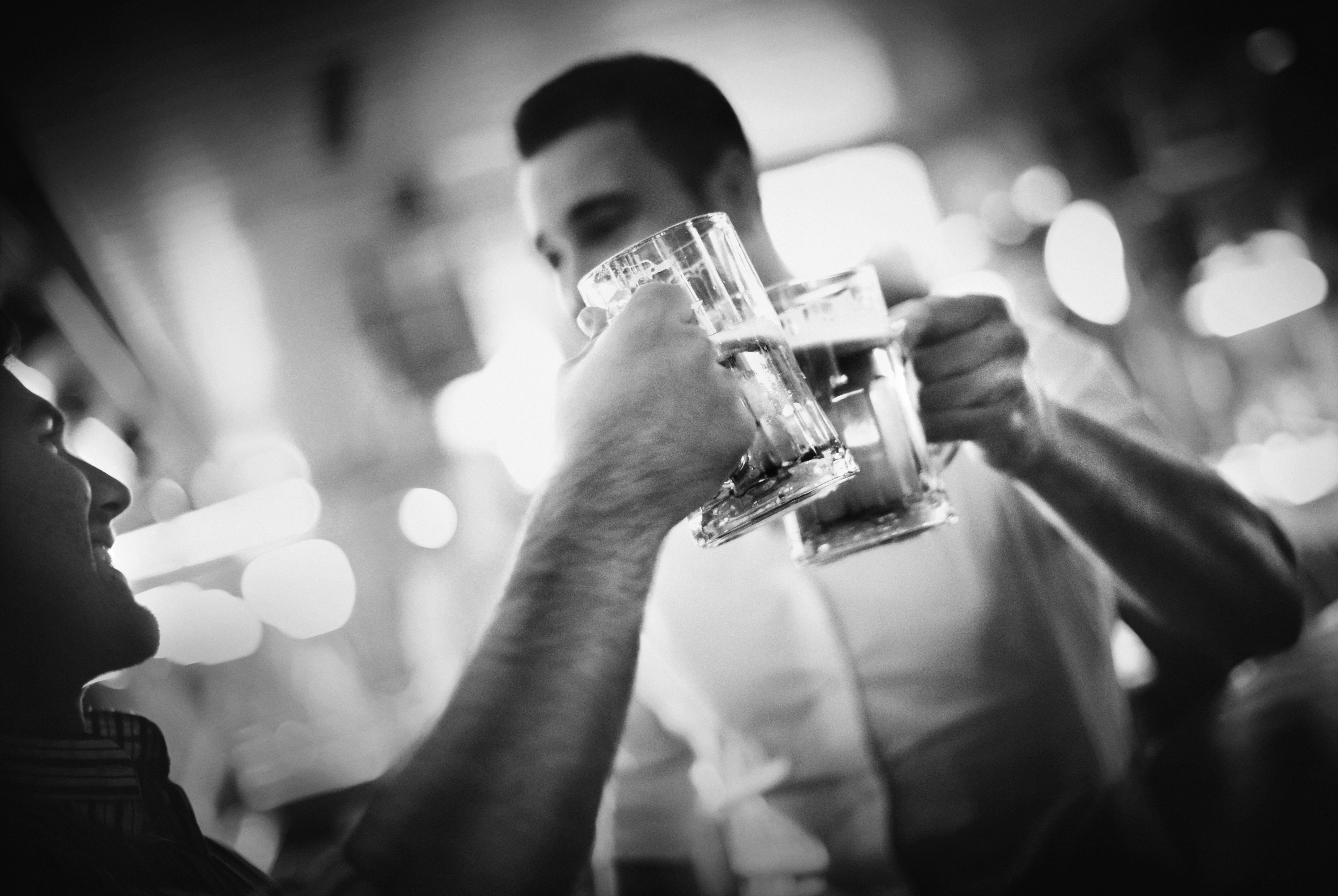 Two middle aged men having beer in a bar.They are toasting with beer mugs.Relaxed weekend night out.Black and white.