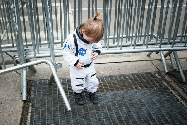 A child wears a National Aeronautics and Space Administration (NASA) costume during the March for Science rally on Earth Day