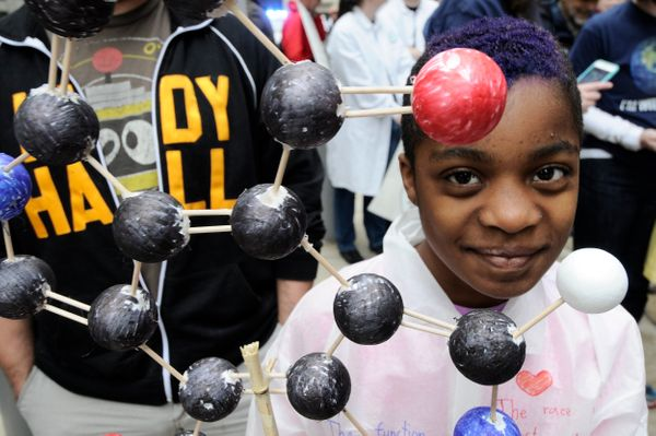 Claudia Levin-Dorko, 9, of Philadelphia, shows a model of a Melanin molecule as he participates with his family in the Nation