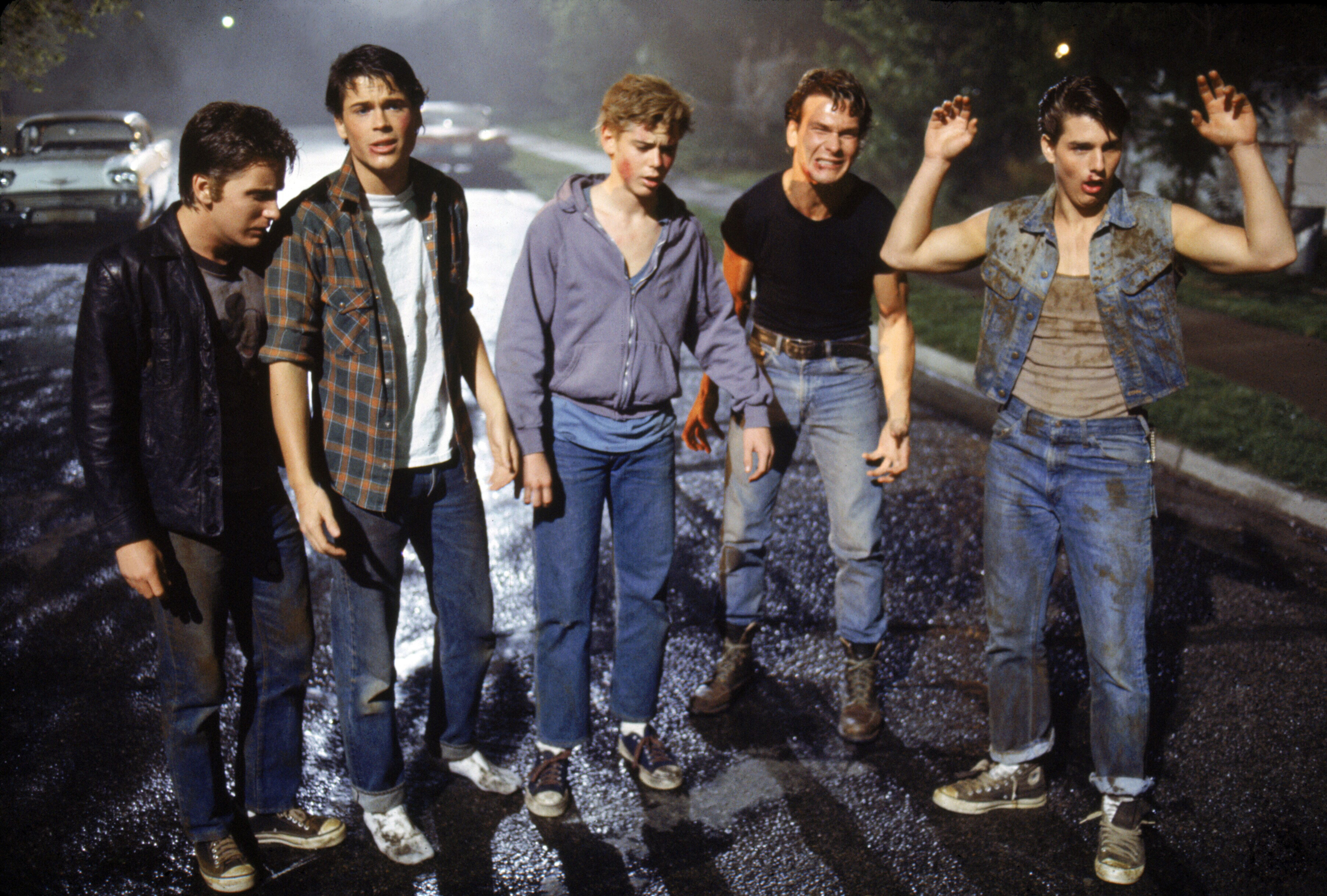 "American actors Emilio Estevez, Rob Lowe, Thomas C. Howell, Patrick Swayze, and Tom Cruise on the set of ""The Outsiders,"" dir"