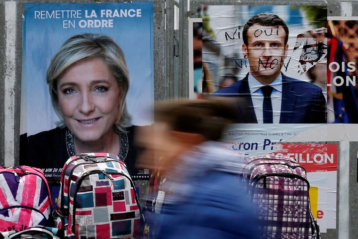 A woman walks past official posters of candidates for the 2017 French presidential election at a local market in Bethune, Fra