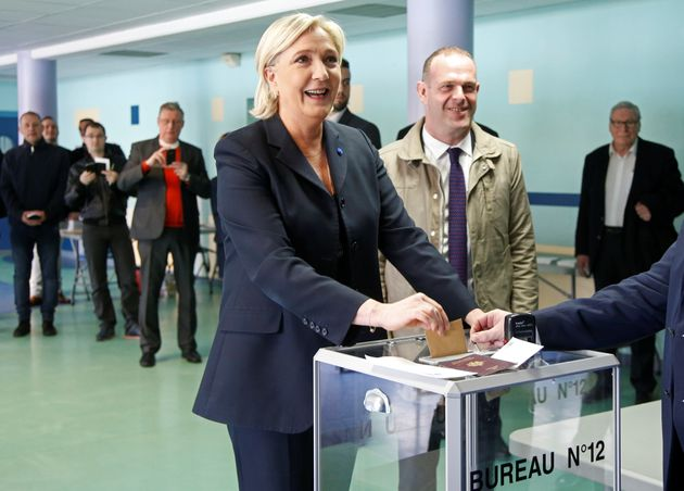 Marine Le Pen (L), a candidate for France'spresidential election, casts her ballot in the first...