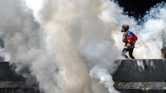 Venezuelan opposition activists clash with police forces during a demonstration against President Nicolas Maduro in Caracas, on April 24, 2017. Protesters rallied on Monday vowing to block Venezuela's main roads to raise pressure on Maduro after three weeks of deadly unrest that have left 21 people dead. Riot police fired rubber bullets and tear gas to break up one of the first rallies in eastern Caracas early Monday while other groups were gathering elsewhere, the opposition said.  / AFP PHOTO / JUAN BARRETO        (Photo credit should read JUAN BARRETO/AFP/Getty Images)