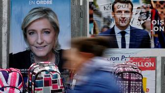 A woman walks past official posters of candidates for the 2017 French presidential election Marine Le Pen, French National Front (FN) political party leader (L) and Emmanuel Macron, head of the political movement En Marche !, or Onwards !, (R) at a local market in Bethune, France, April 24, 2017.  REUTERS/Pascal Rossignol