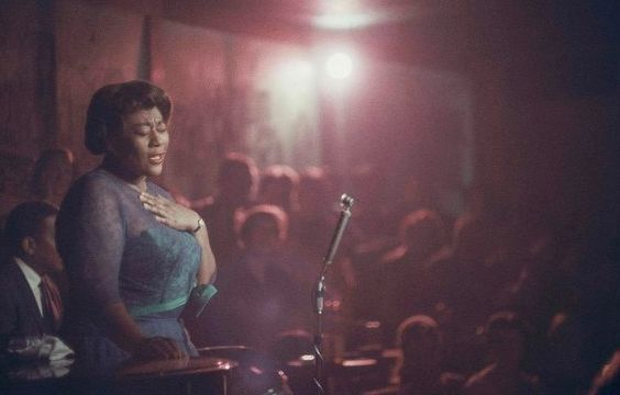 "Bathed in red light, Ella Fitzgerald performs with her eyes closed at Mr. Kelly&rsquo;s nightclub in Chicago, 1958.<a href=""h"