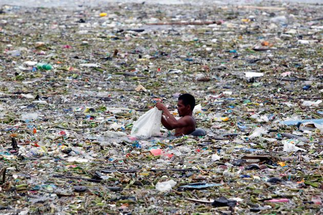 A man collects plastic and other recyclable materials from debris in the waters of Manila Bay after tropical...