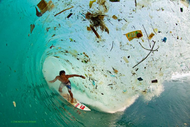 Photographer Zak Noyle capturesa surfer riding a trash-filled wave in waters off the coast of Java, Indonesia.