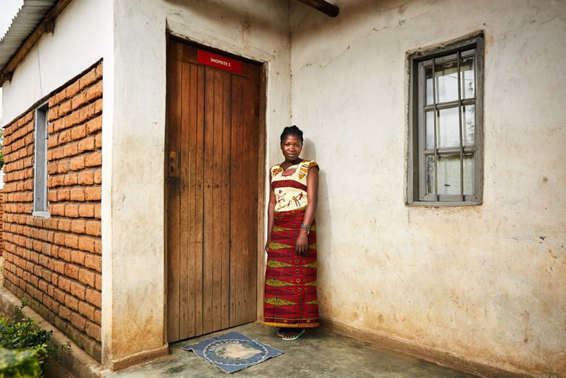 Happiness (17) stands next to the front door of her gowelo, Thyolo District, Malawi, 2016. She has lived here since 2015. Lik