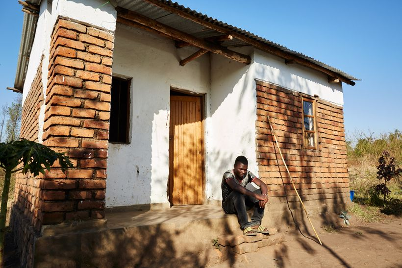 Peter (17), sits on the porch of his gowelo, Thyolo District, Malawi, 2016. After his parents died, Peter was found by a soci