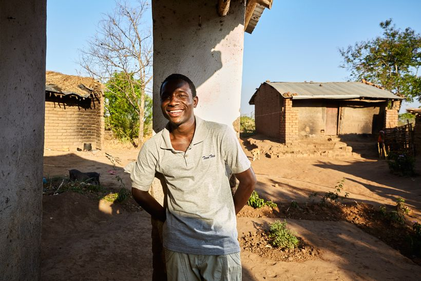 """John (18) stands on the porch of his gowelo, Thyolo District, Malawi, 2016. John's parents died in a car accident in 2005. """"W"""