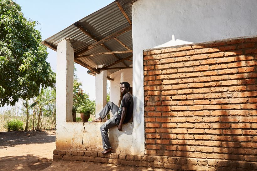 James (19) sits on the porch of his gowelo, Thyolo District, Malawi, 2016. James was very young when his father died. Althoug