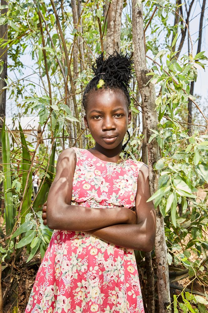 Maureen (11) poses in the garden next to her gowelo, Thyolo District, Malawi, 2016.